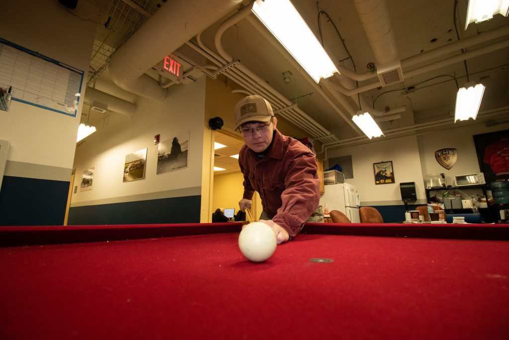 Young man about to strike a billiards ball inside an industrial room