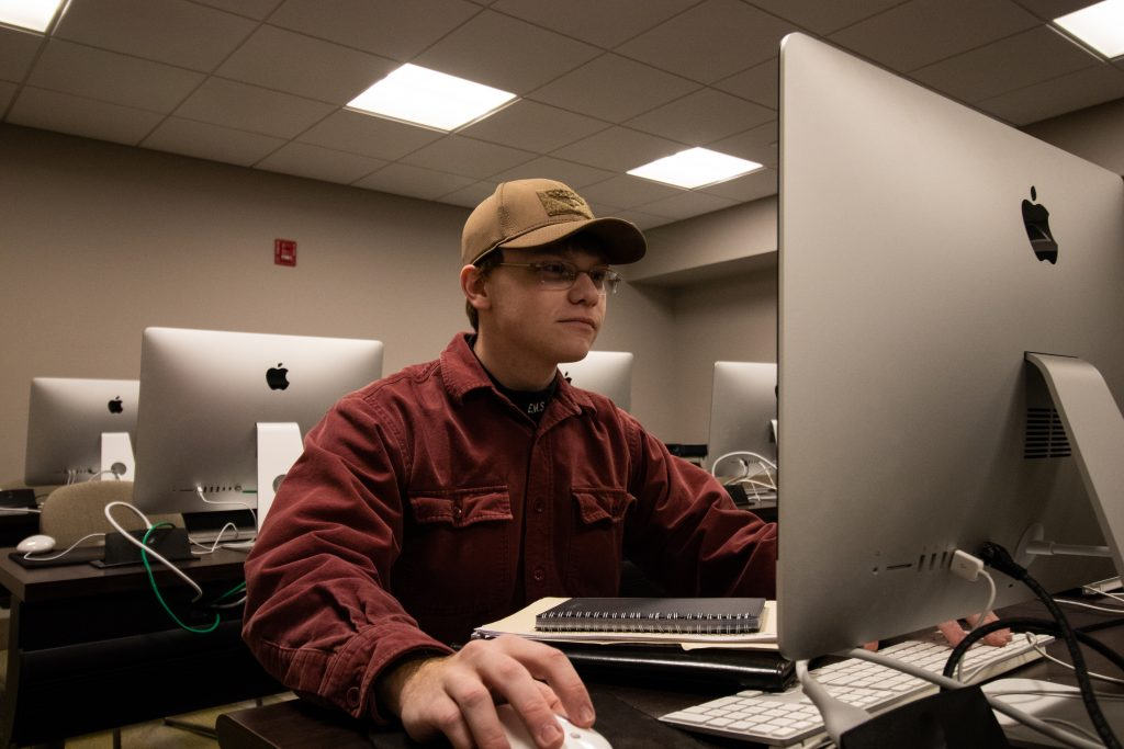 Young man in red button down shirt working on desktop computer