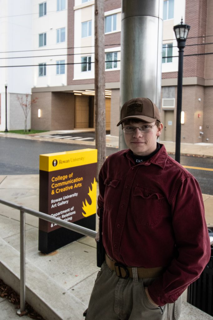 Young man standing outside, leaning against a metal column with a yellow and brown sign in the brackground