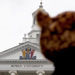 blurred figure in foreground with Rowan University brick and marble building in background