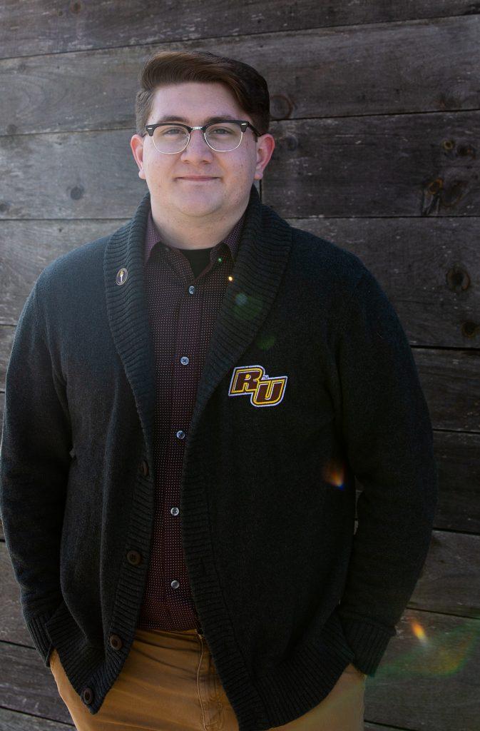 Brandon in front of wood background in Rowan sweater