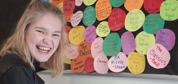 Nicole Grant laughs as she stands in front of a colorful bulletin board she made as a resident assistant.