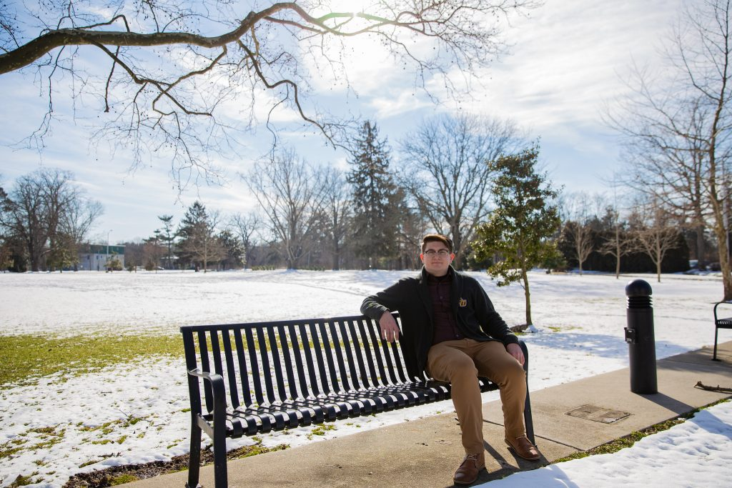 Brandon sitting on bench outfront Bunce Green with snow on ground
