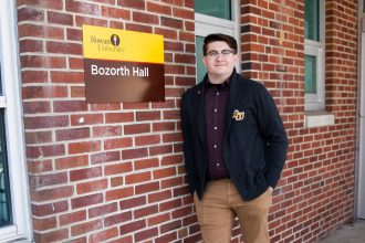 Brandon outside Bozarth Hall in Rowan sweater, in front of brick wall