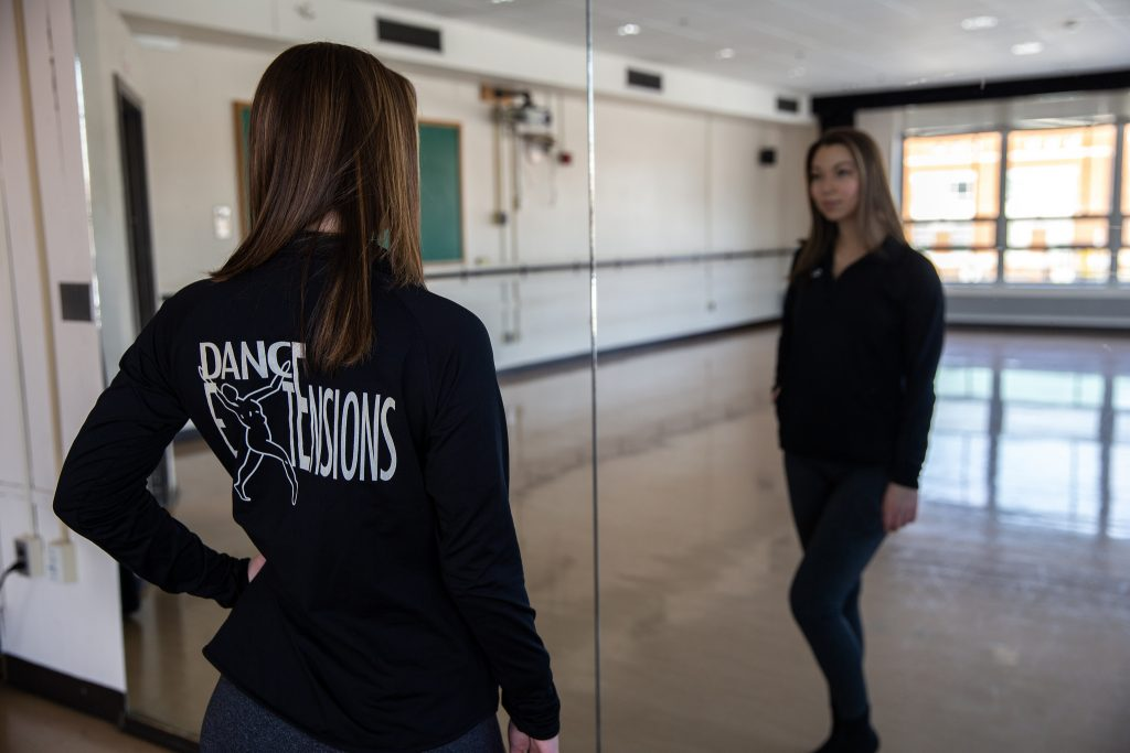 Haley in Dance Extensions hoodie looking into mirror in the dance studio