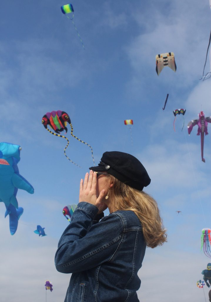 photo Kailey took of a female holding her hat facing away with the blue sky and kites in the background