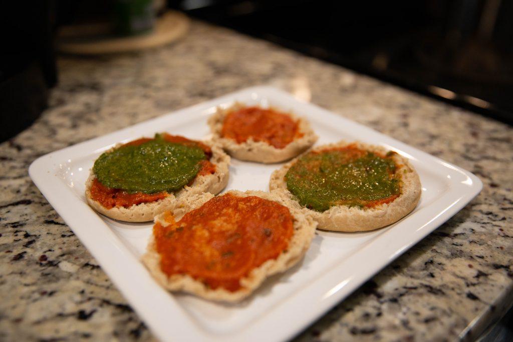 Halved english muffins topped with marinara and pesto sauce.