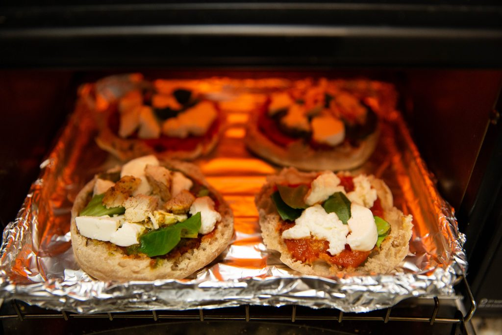 English muffin pizzas placed in toaster oven.