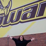 Kara outside of Rowan Sign holding her hands up in the air