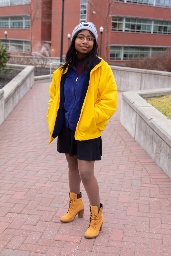A rowan student in a beanie, yellow jacket and tan boots stands by Savitz hall