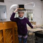 Student Isabel wearing a prop hat inside the rehearsal room