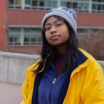 A student wearing a beanie, yellow jacket and blue sweater