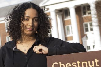 Vanessa from Rowan University stands in front of the sign for Chestnut Hall dorm, with her left elbow resting on the brown sign