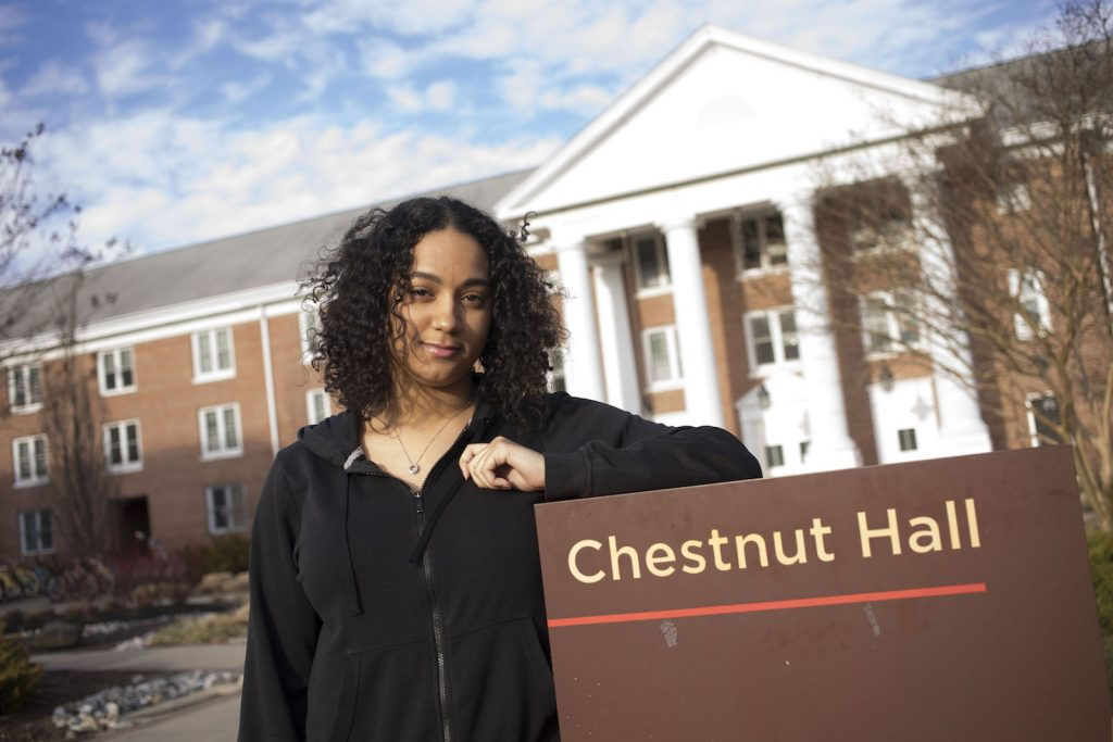 Vanessa stands with her left elbow resting on the Chestnut Hall sign in front of her dorm