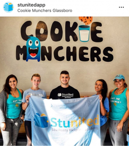 John Rondi and team inside Cookie Munchers on the Rowan Blvd holding their Stunited flag