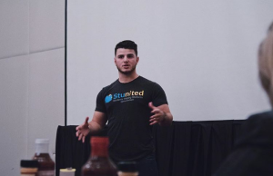 John Rondi speaking at an event in his Stunited teeshirt inside