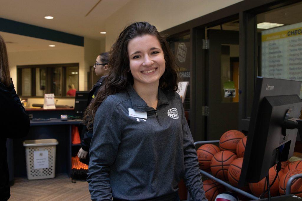 Laura Bartoli posing behind Rowan's Rec Center's desk.