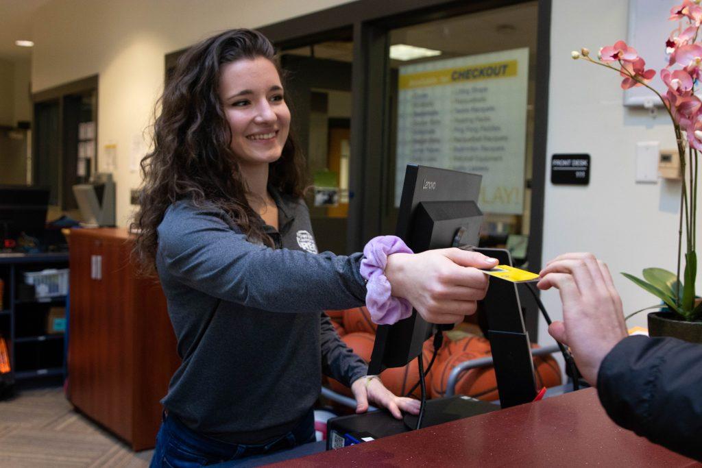 Laura Bartoli handing Rowan student their student ID.
