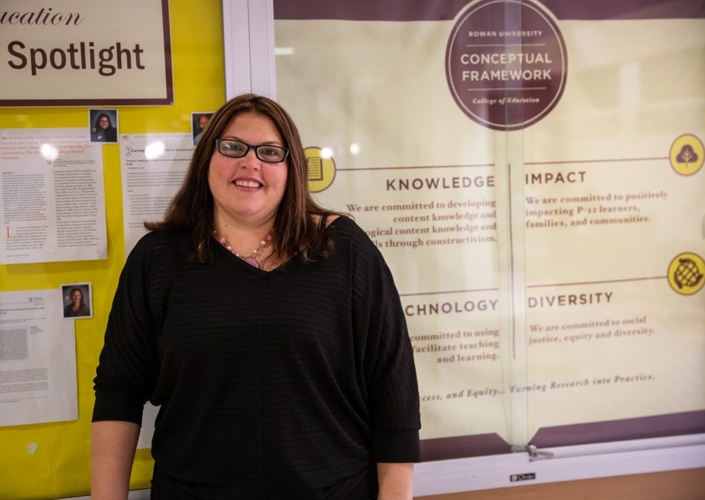 Dr. Ieva standing inside James Hall next to Faculty Spotlight board