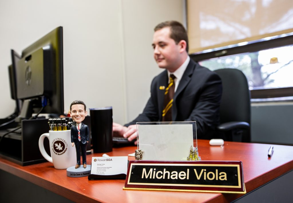 Mike typing at his desk inside the student center with a desk name plate Michael Viola in focus