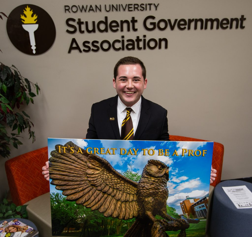 Mike holding a Profs sign inside the Student Government Association office in a black suit