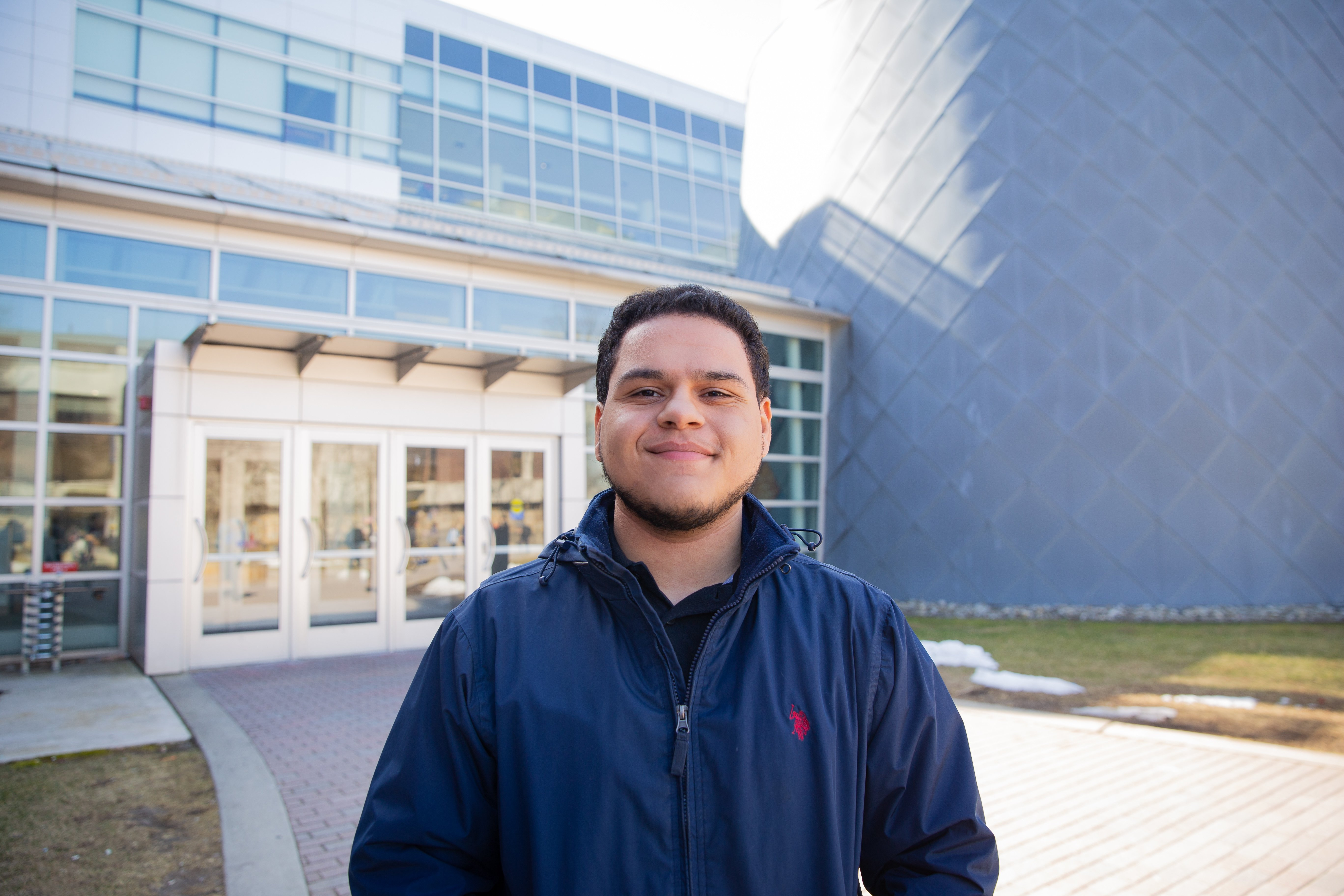 Luis Acevedo posing outside the science building at Rowan University.