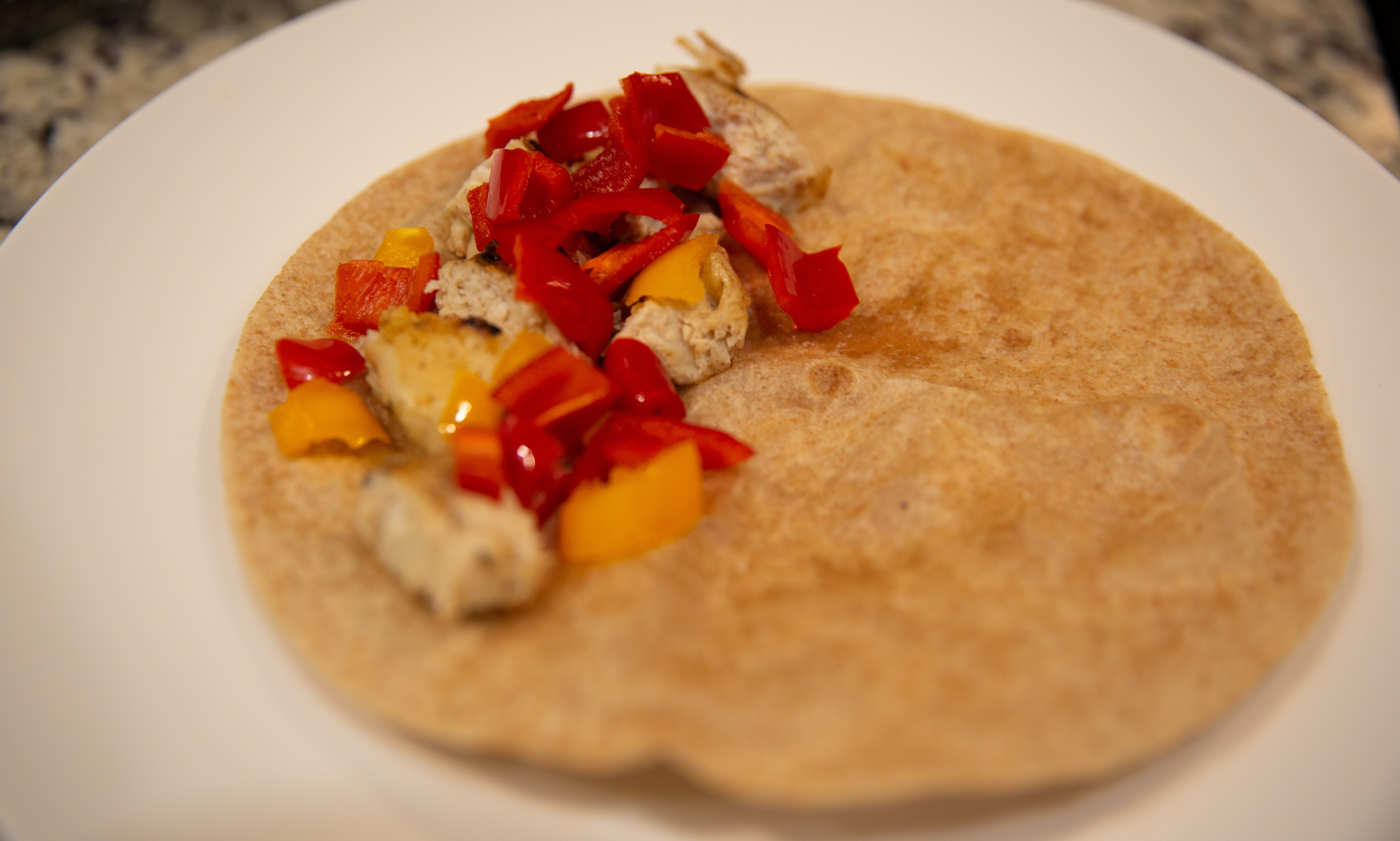 Tortilla with chicken and peppers on it.