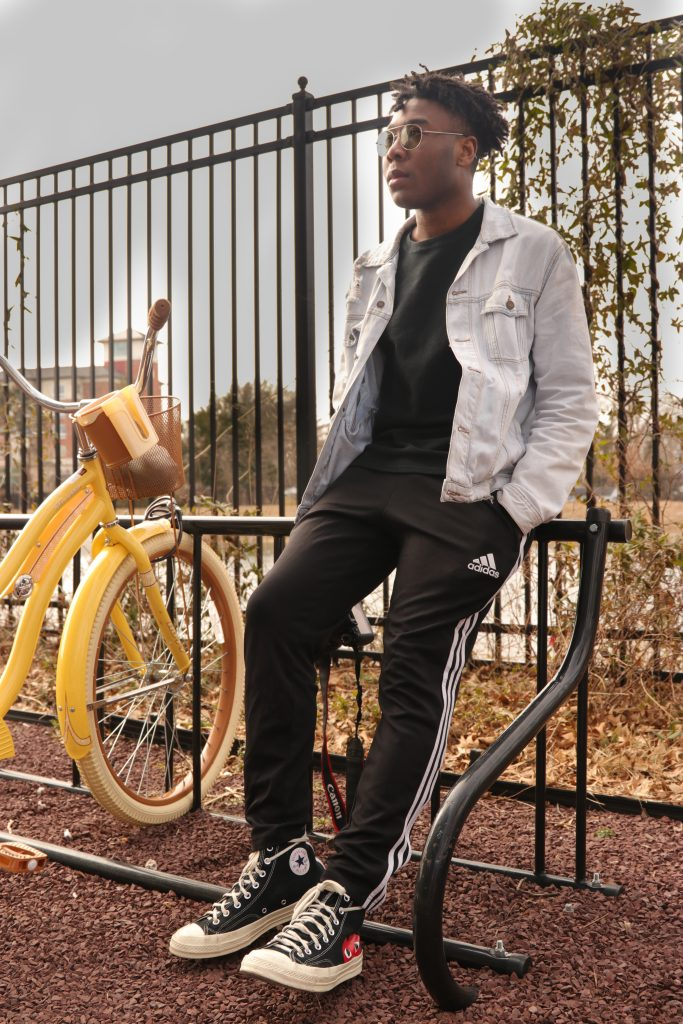 Jelani leans against a fence, hands in his pockets, with bikes next to him.