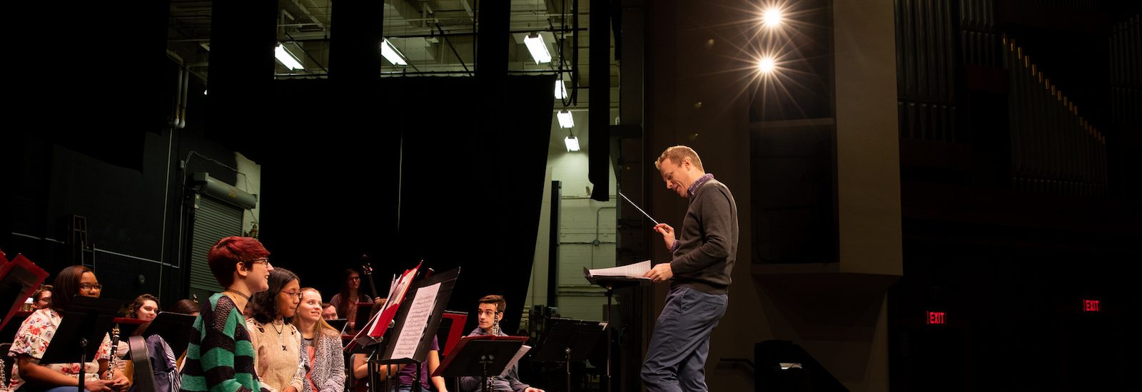 Professor Higgins conducting the ensemble on stage in Pfleeger Hall
