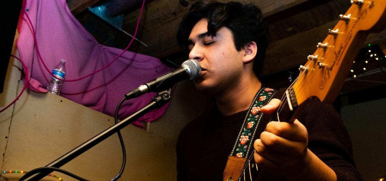 Enzo, Rowan student, playing guitar at a show near Rowan