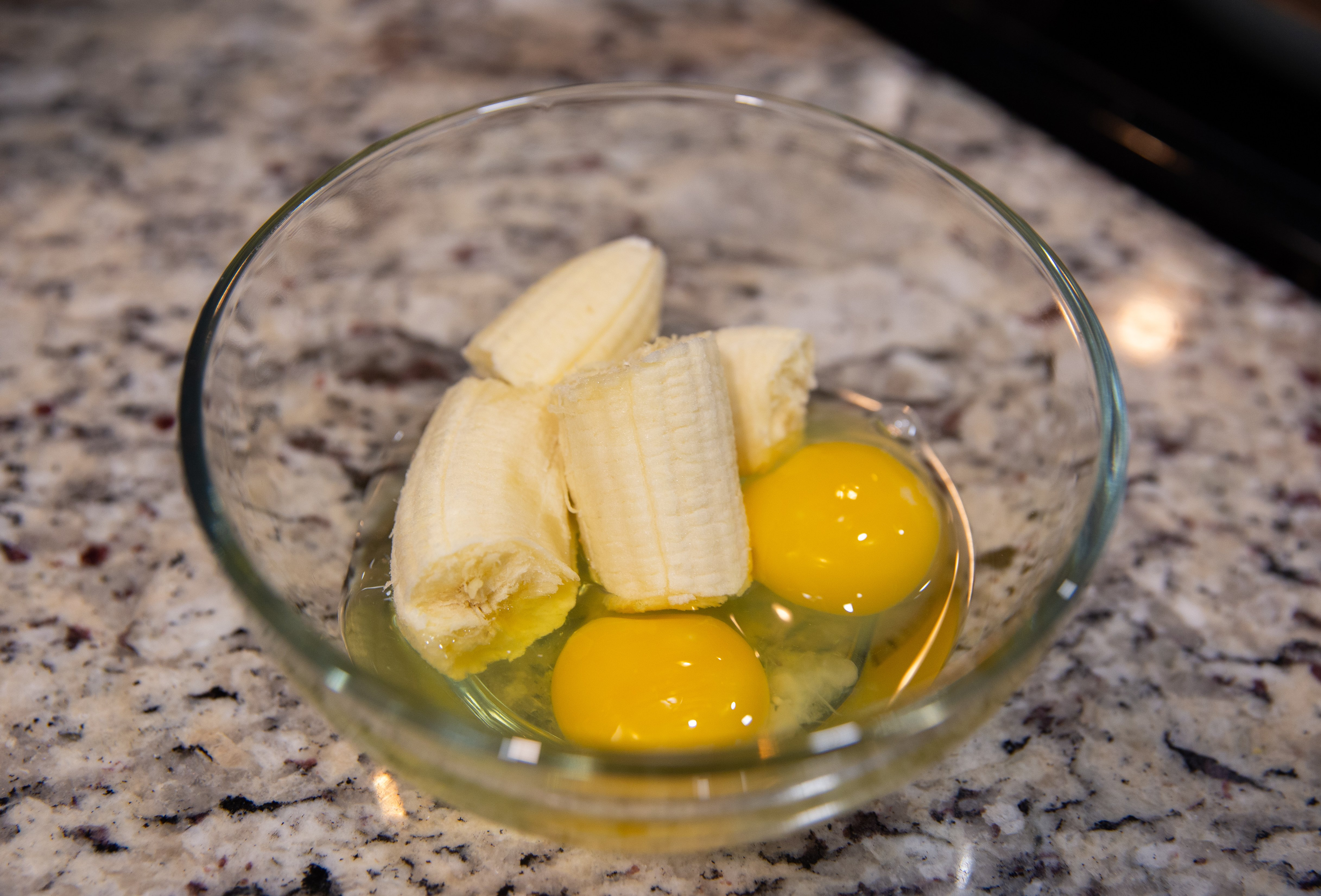 Close up of the cracked eggs and broken banana in a bowl.
