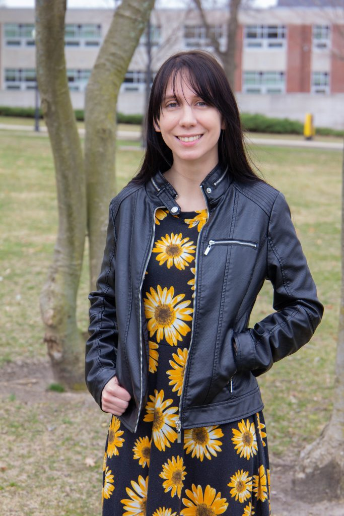 Jen Green stands in the grass in front of Hawthorn Hall, wearing a leather jacket and a black dress with sunflowers.