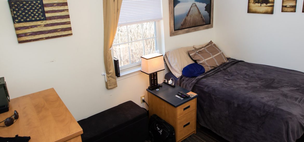 Inside student dorm with one bed, a side table, a dresser, and several pictures on the walls
