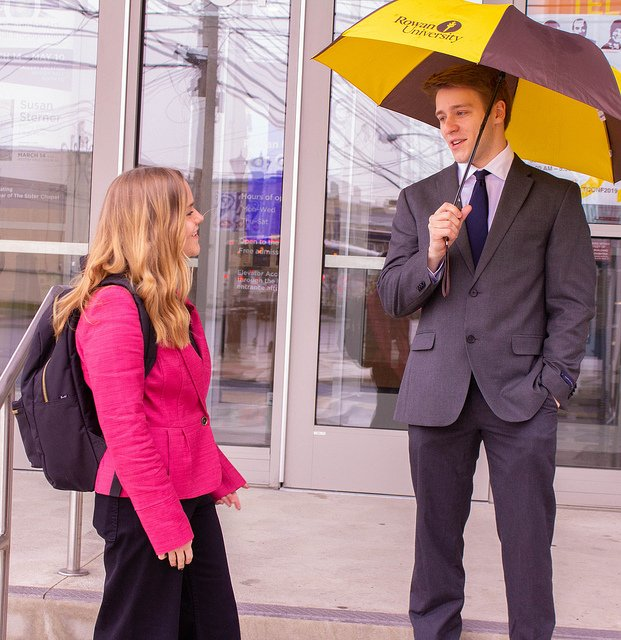 kailey and tim of Rowan University discuss their project outside the communication building as tim holds a rowan university umbrella