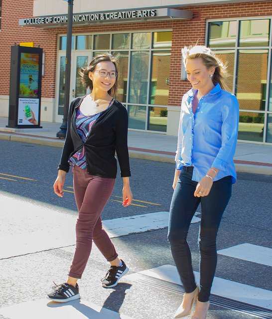 Brittany and Megan of Rowan University cross the street in a crosswalk outside the communication building