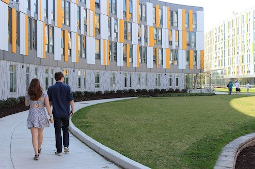 Two students walk on the sidewalk inside the curve of Holly Pointe Commons.