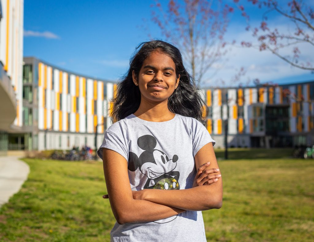 Prasheetha standing out front of holly pointe outside in a Mickey Mouse shirt