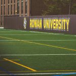 Rowan University sign showing on the athletics field