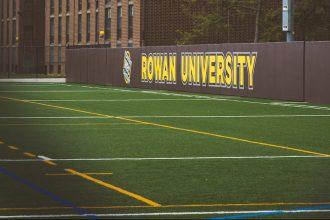 Rowan University sign showing on the athletics field