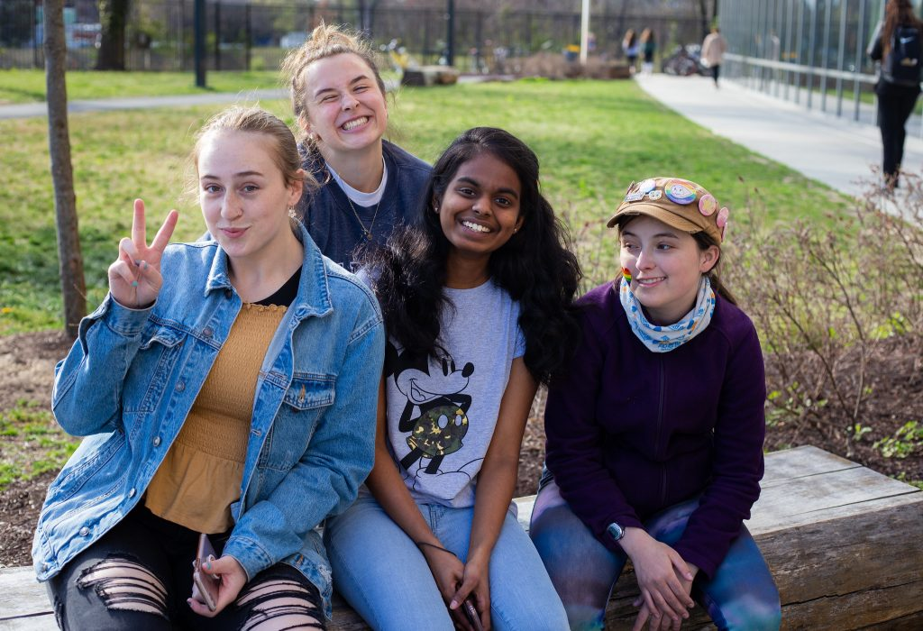 Prasheetha and three other students sitting on the bench outside of Holly Pointe