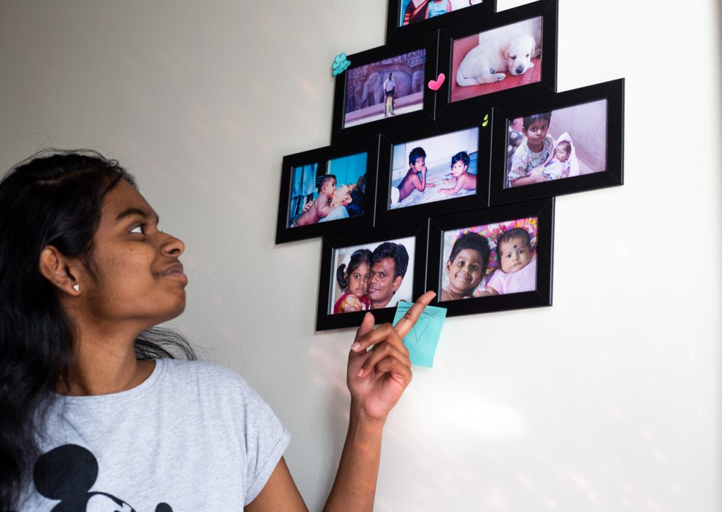 Prasheetha pointing to photos from her home country hanging on her dorm wall