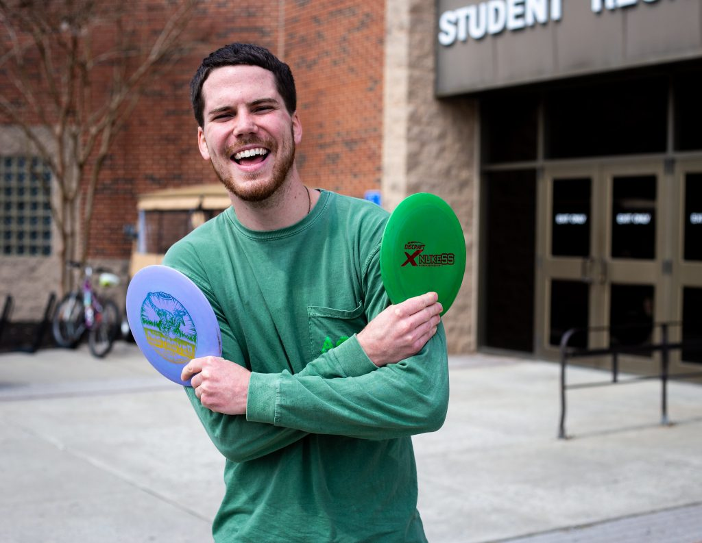 Austin out front of the Rec center holding up frisbees