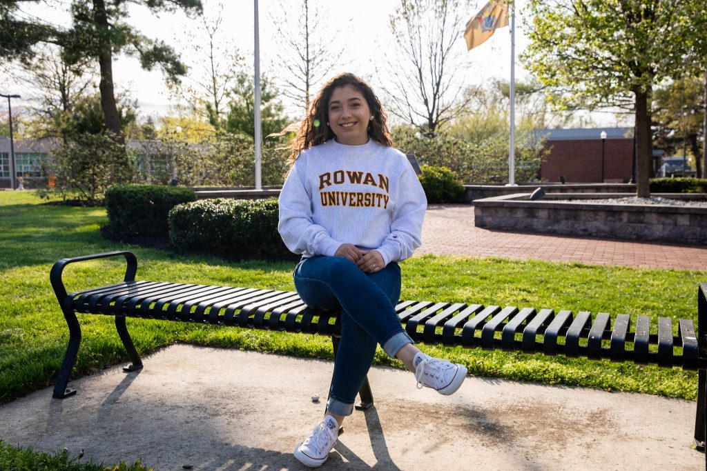 Allison wearing Rowan hoodie sitting on bench outside of Bunce