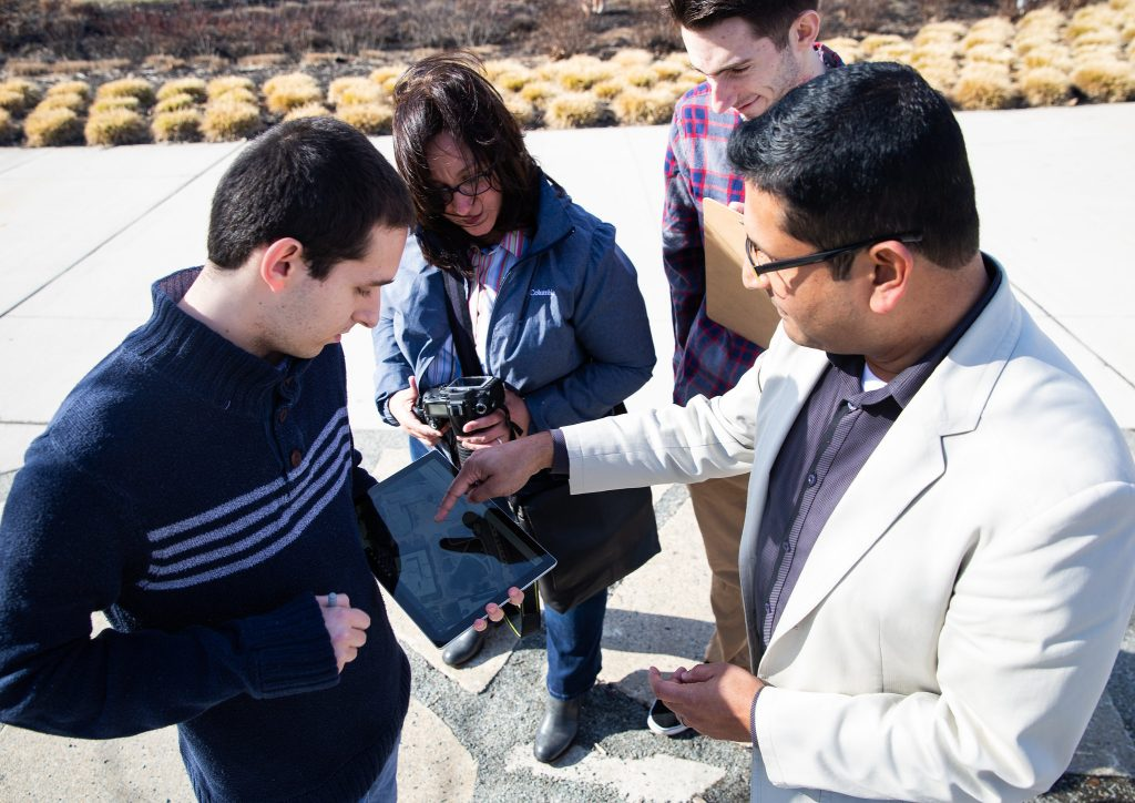 Dr. Meenar pointing to a camera outside with students