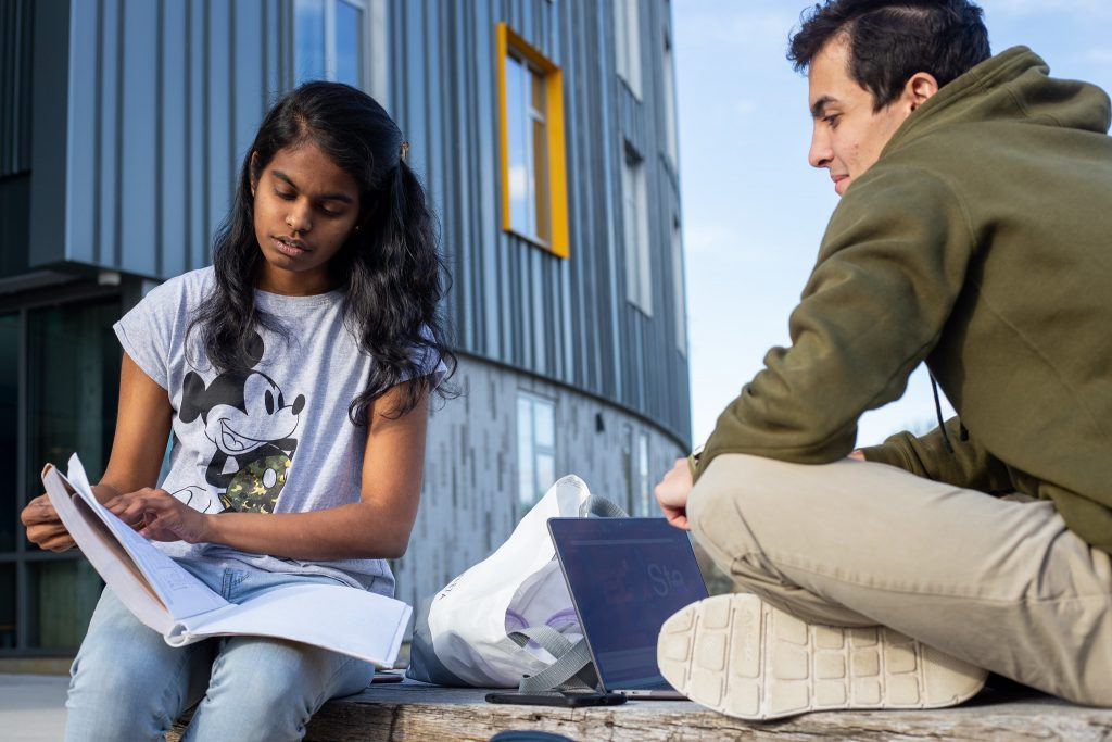 Prasheetha studying with her friend outside with a book and laptop