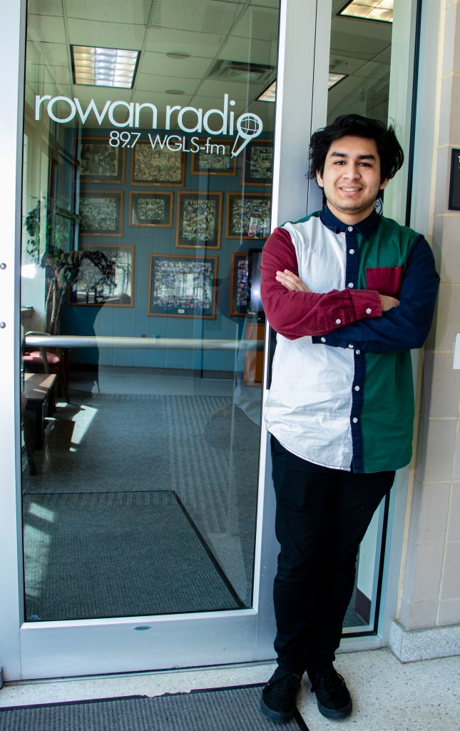 young male student standing in front of glass door with Rowan Radio, 89.7 WGLS-fm written on it
