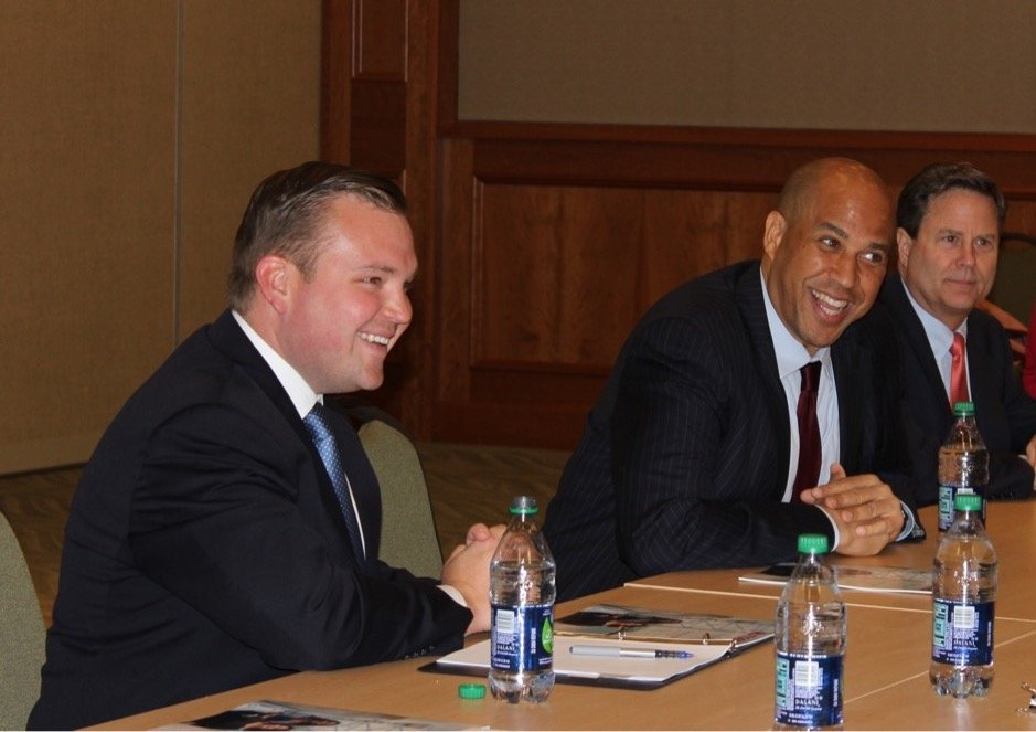 Bill Moen sits at a conference table next to Cory Booker.