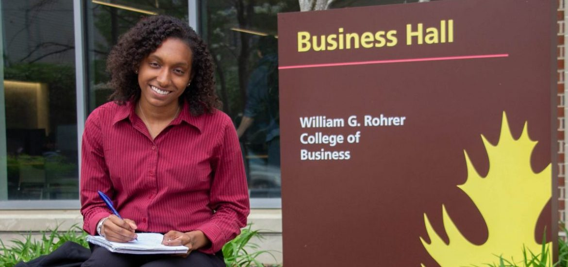 Jo Carter sits next to a Business Hall sign at Rowan University, wearing a pink button down blouse and holding a notebook