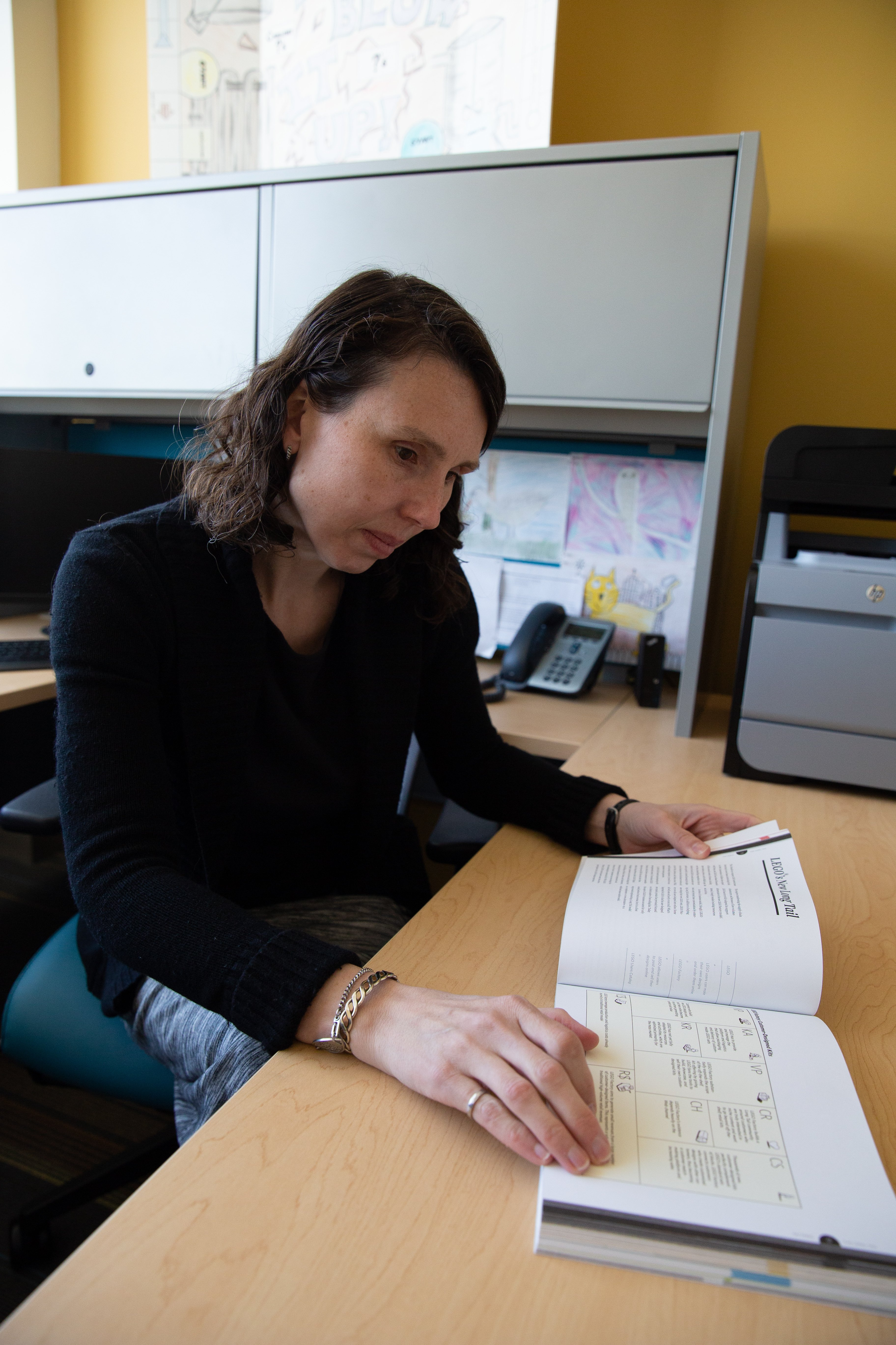 Dr. Cheryl Bodnar flipping through a book in her office at the engineering building.