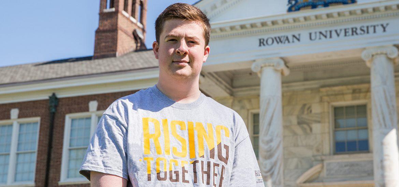 Jason, wearing a Rising Rowan shirt, standing outside Bunce Hall